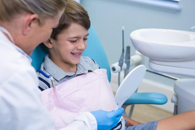 Dentysta pokazuje chłopcu lustro