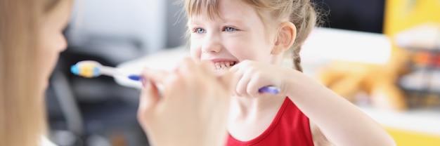 Dentysta pokazuje dziewczynie, jak prawidłowo myć zęby