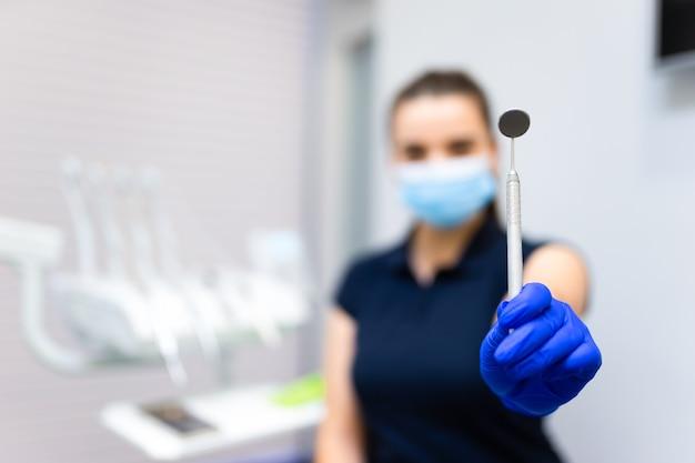 Dentysta pokazuje lusterko do badania jamy ustnej