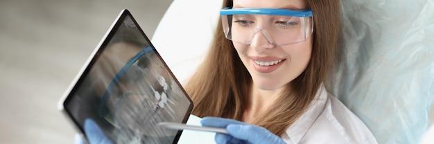Dentysta pokazuje pacjentowi zdjęcie rentgenowskie szczęki kobiety na tablecie