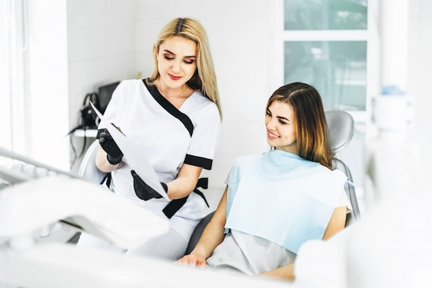 Dentysta pokazuje promieniowanie rentgenowskie dla pacjenta i wyjaśnia plan leczenia.