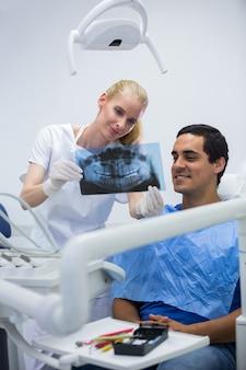 Dentysta pokazuje stomatologicznego promieniowanie rentgenowskie pacjent