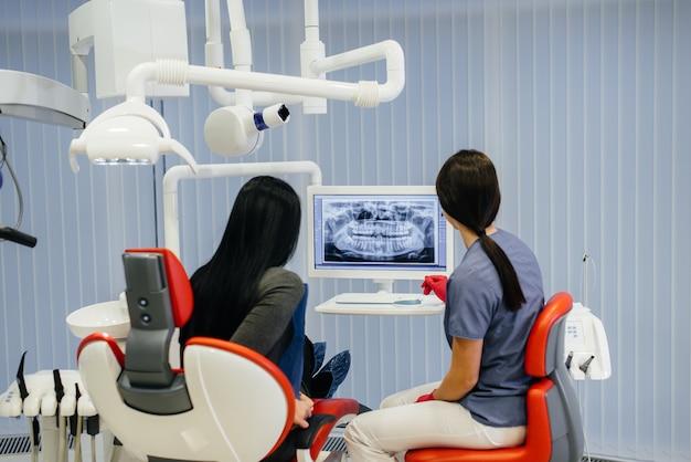 Dentysta pokazuje zdjęcie zębów pacjenta i informuje o koniecznym leczeniu