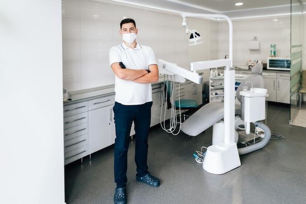 Dentysta pozuje w biurze z chirurgicznie maską