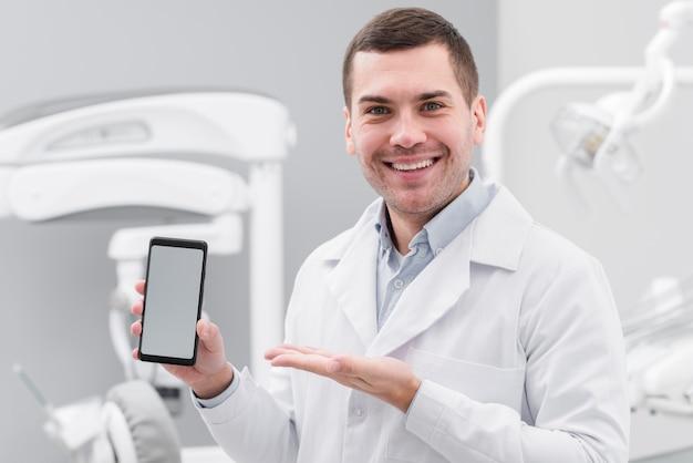 Dentysta przedstawiający smartphone