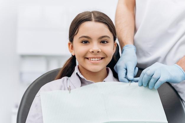 Dentysta przygotowuje małego pacjenta do leczenia stomatologicznego. atrakcyjna mała dziewczynka uśmiecha się szczęśliwie