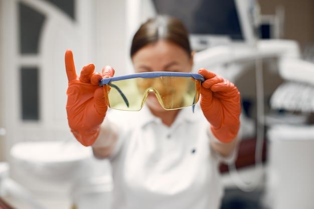 Dentysta przygotowuje się do przyjęcia, lekarz trzyma okulary, kobieta w gumowych rękawiczkach