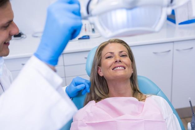 Dentysta regulujący oświetlenie elektryczne, gdy pacjent siedzi na krześle