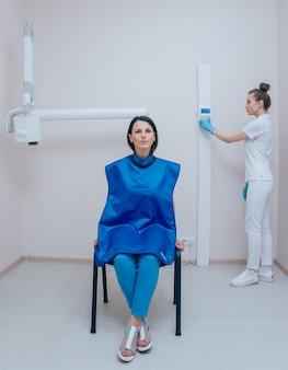 Dentysta robi zdjęcie rentgenowskie dla młodej kobiety w klinice dentystycznej. celowanie radiografii stomatologicznej.