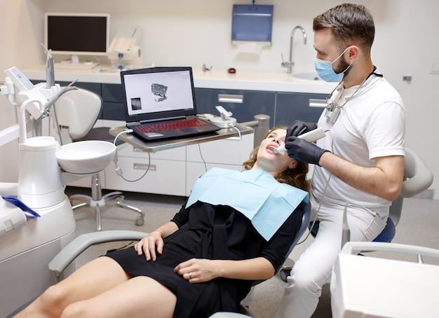 Dentysta skanuje zęby pacjenta za pomocą skanera 3d.