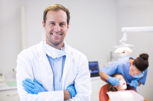 Dentysta stojący z rękami skrzyżowanymi w klinice