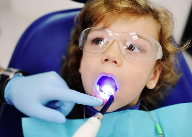 Dentysta świeci na zęby dziecka specjalną lampą do wypełnień stomatologicznych