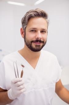 Dentysta trzyma pincety dentystyczne i lustro w ustach