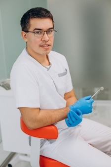 Dentysta ubrany w biały mundur w klinice