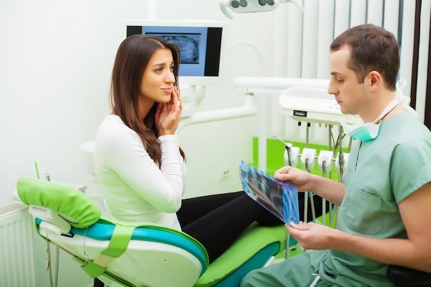 Dentysta w gabinecie stomatologicznym rozmawia z pacjentki i przygotowuje się do leczenia