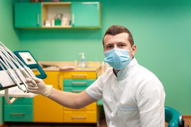 Dentysta w masce bierze wiertło