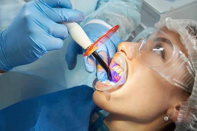 Dentysta w rękawiczce z lampą utwardzania dentystycznego pracuje z klientem