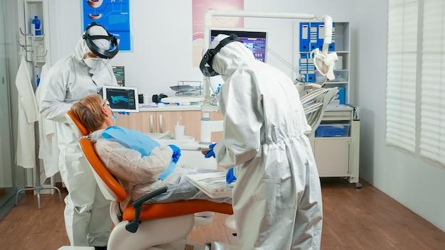 Dentysta w sprzęcie ochronnym pokazujący na tablecie rtg dentystyczne przeglądanie go ze starszym pacjentem. zespół medyczny noszący kombinezon z osłoną twarzy, maskę, rękawiczki, wyjaśniający radiografię za pomocą wyświetlacza notebooka;