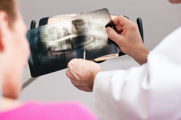 Dentysta wyjaśnia promieniowanie rentgenowskie pacjentowi