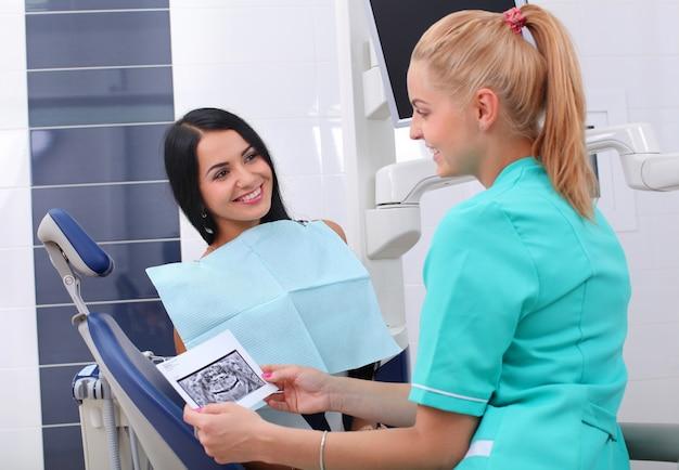 Dentysta wyjaśniając zdjęcie rentgenowskie pacjentowi.