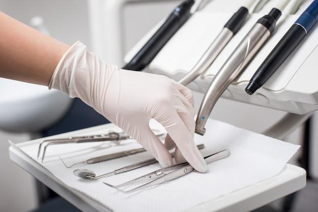 Dentysta z dłonią w rękawiczce wybiera pincety dentystyczne w gabinecie stomatologicznym. z bliska, selektywne focus. stomatologia