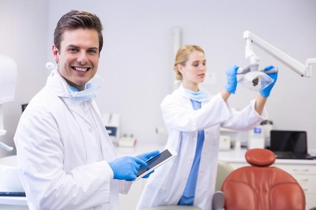 Dentysta za pomocą cyfrowego tabletu, podczas gdy jego kolega reguluje lampę główną