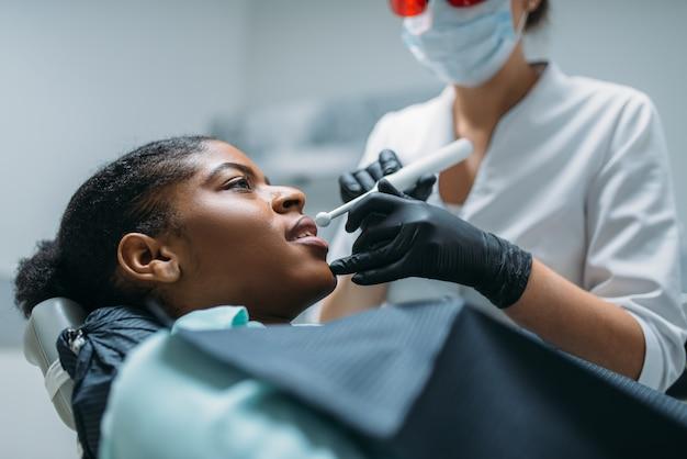 Dentysta zakłada pieczęć na ząb, gabinet dentystyczny