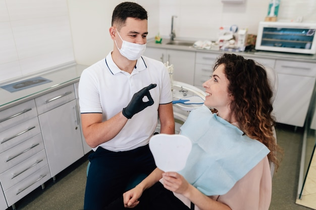 Dentysta zatwierdzając uśmiech pacjenta