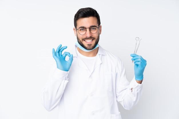 Dentysty mężczyzna mienia narzędzia na biel ścianie pokazuje ok znaka z palcami