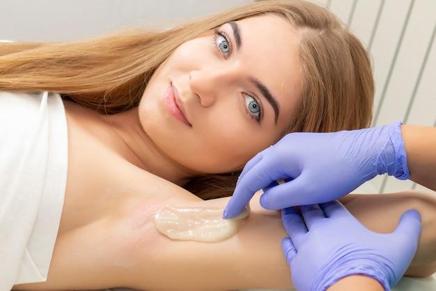 Depilacja cukrem upłynnionym pod pachami. mistrz słodzenia w procedurze usuwania włosów dla kobiet. depilacja likierową pastą cukrową