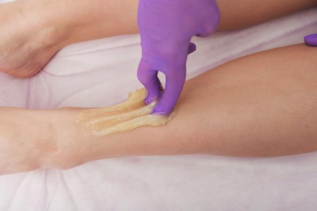 Depilacja cukrowa pielęgnacja skóry z płynnym cukrem na nogach