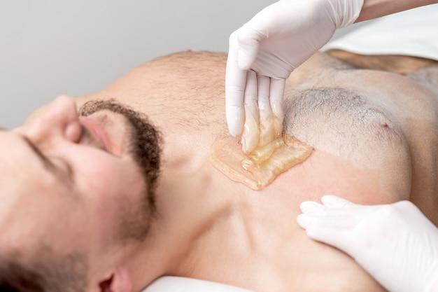 Depilacja klatki piersiowej młodego mężczyzny za pomocą płynnej pasty woskowej przez ręce kosmetyczki w salonie piękności