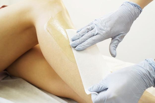 Depilacja pięknych kobiecych nóg. woskowanie w salonie kosmetycznym. zbliżenie lekarza ręce w rękawiczkach