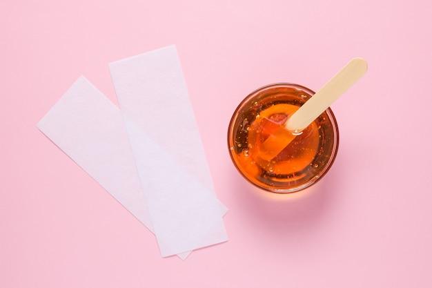 Depilacyjna pasta cukrowa z drewnianą szpatułką i paskami do depilacji na różowym tle