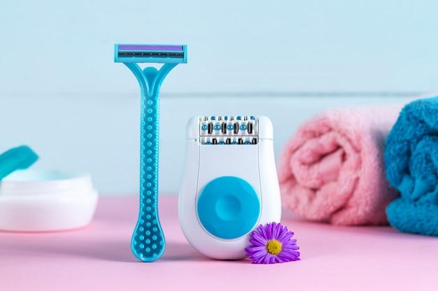 Depilator, krem, brzytwa dla kobiet, ręczniki i kwiaty. epilacyjny. usuwanie niechcianych włosów. koncepcja depilacji