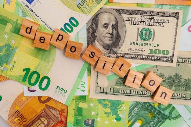 Depozycja napis na drewnianych kostkach na fakturze dolarów amerykańskich i banknotów euro