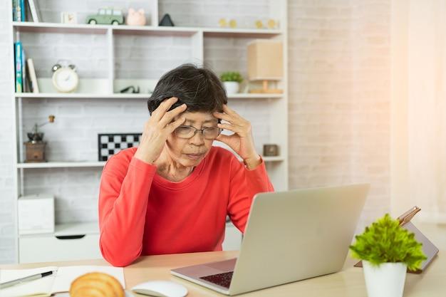Depresja starszej kobiety i poważne myślenie o sprawdzaniu wykresu cen bitcoin na cyfrowej giełdzie na laptopie