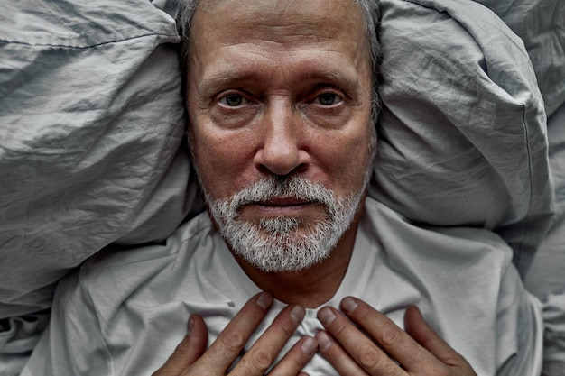 Depresyjny mężczyzna leży samotnie w łóżku, cierpi na samotność, bez sensu życia