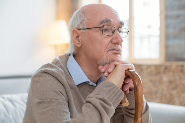 Depresyjny nastrój. przystojny odblaskowy starszy mężczyzna opierając się na lasce w okularach i pozowanie na niewyraźne tło