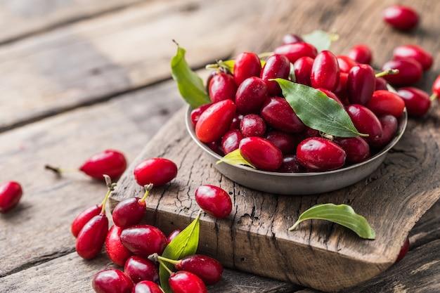 Dereń w talerzu na drewnianym tle. zbieranie letnich zbiorów. czerwona jagoda.