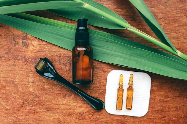 Dermaroller i serum obok przeciwzmarszczkowego kremu do twarzy przemysł kosmetyczny zbliżenie dermaroller do mikroigłowej terapii medycznej
