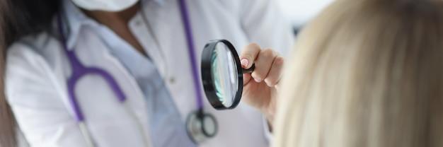 Dermatolog bada twarz pacjenta przez szkło powiększające problemy ze skórą twarzy