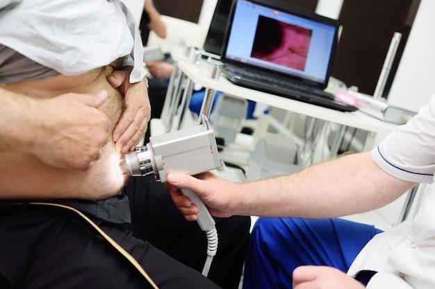 Dermatolog bada za pomocą dermatoskopu pieprzyki lub trądzik pacjenta. zapobieganie czerniakowi