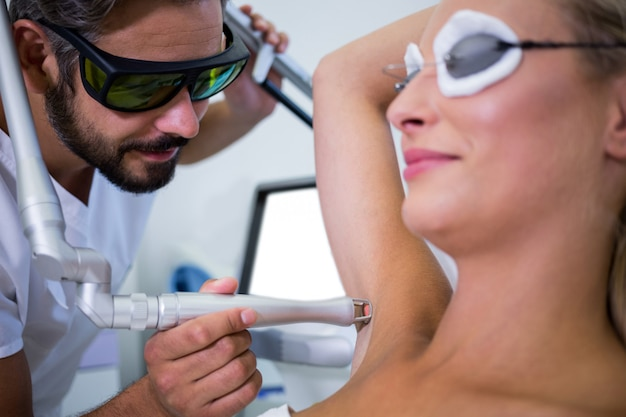 Dermatolog usuwający włosy pod pachą pacjenta