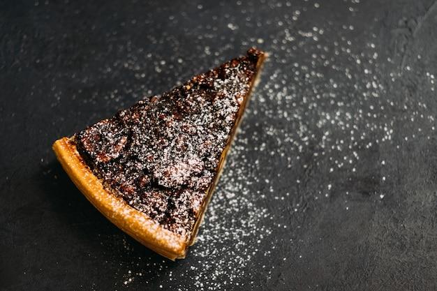 Deser ciasta. tarta orzechowa z melasą posypana cukrem pudrem.