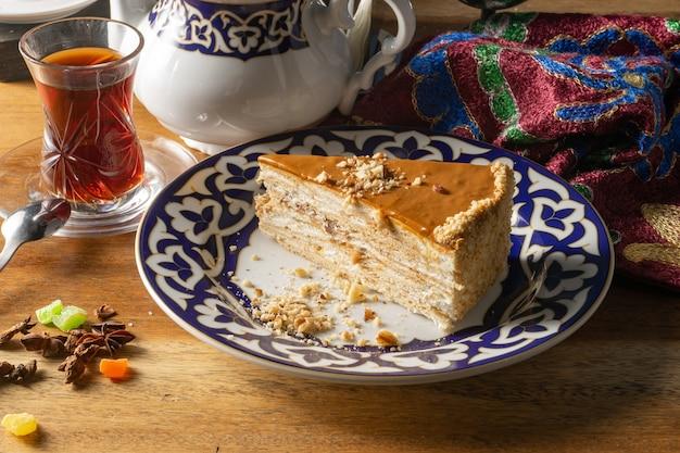 Deser ciasto miodowe. klasyczne ciasto z miodowych ciastek nasączonych śmietaną na tradycyjnym uzbeckim talerzu