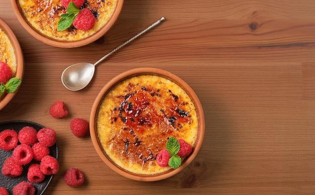 Deser creme brulee z malinami i liśćmi mięty na drewnianym stole, widok z góry z miejscem na kopię. pyszny deser ze śmietaną i karmelizowanym cukrem