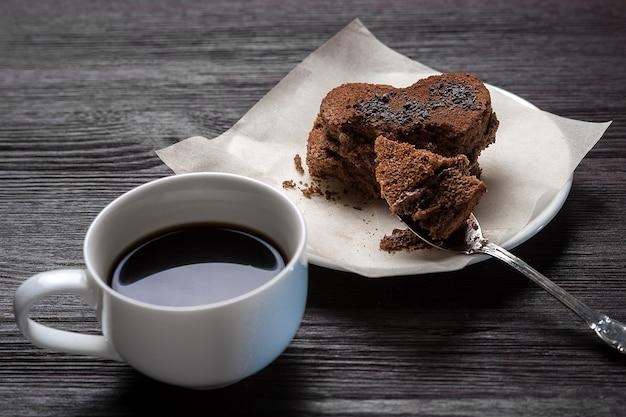 Deser czekoladowy w formie serca na białym spodku obok filiżanki pachnącej kawy stoi na drewnianym starym tle
