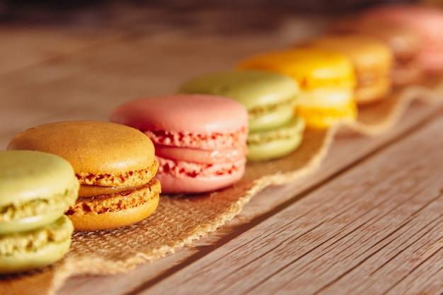 Deser francuskich makaroników w pastelowych kolorach na drewnie copy space selektywne skupienie