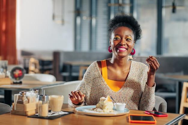 Deser i latte wesoła, atrakcyjna kobieta delektująca się pysznym deserem i latte w stołówce
